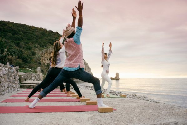 yogis practicing yoga on a beach in Montenegro